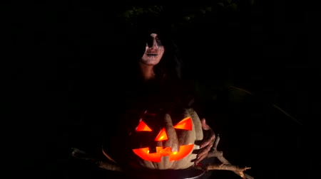 wicked : Wicked frightening witch hexing with red eye pumpkin in dark forest . Halloween Horror Scene Stock Footage