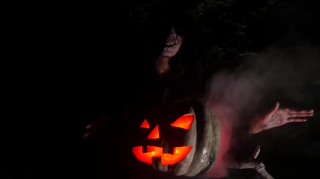 boszorkány : Wicked frightening witch hexing with red eye pumpkin in dark forest . Halloween Horror Scene Stock mozgókép