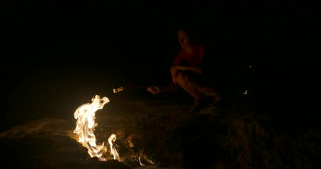 sırt çantasıyla : Young woman roast marshmallow on fire. Natural gas flames burning at Chimera, Yanartas, Cirali, Olympos, Turkey. Stok Video