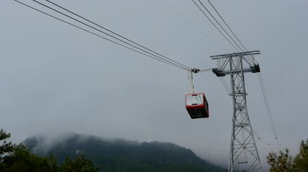 vago : Cable car cabin moving to the station with the mountains in for background. Tahtali Teleferik cable road in Antalya, Turkey
