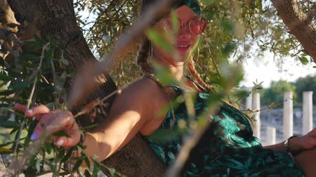 Çingene : Young hippie woman with sunglasses sitting on the tree and smiling to the camera