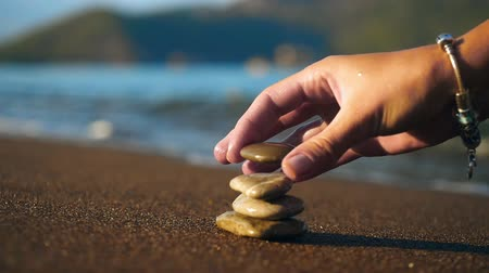 hierarchy : Woman stacked stones at the sand beach close up. There is beautiful landscape view on background Stock Footage