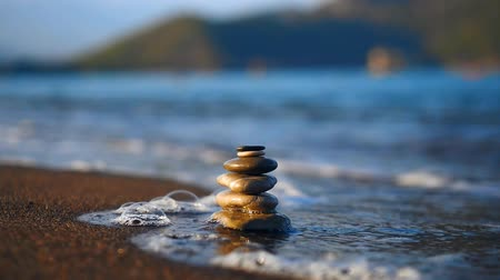 balanceamento : Pile of stones washed by sea tide on sand beach Stock Footage