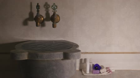 bathhouse : Marble bowl in turkish bath filled with water. Some drop falling from two faucets with cold and hot water in turkish bath. Closeup view Stock Footage
