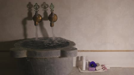 bathhouse : Water flows from two faucets with cold and hot water and out of marble bowl in turkish bath. Closeup view of water flowing