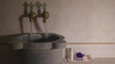 bathhouse : Womans hands open two faucets with cold and hot water in turkish bath. Closeup view of water flowing