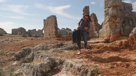 phaselis : Funny young woman archeologist brings big luggage to archaeological site Stock Footage
