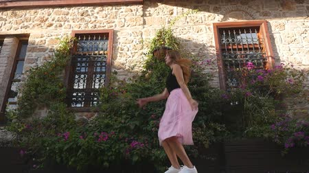 koketa : Fashion lifestyle portrait of young happy pretty woman in pink tulle skirt jumping funnily on street background in slow motion