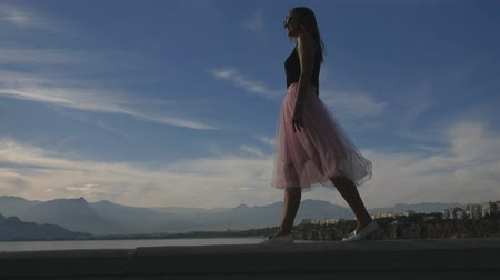 koketa : Fashion lifestyle portrait of young happy pretty woman in pink tulle skirt walking on blue sky background Dostupné videozáznamy