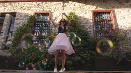infantil : Fashion lifestyle portrait of young happy pretty woman in pink tulle skirt happily dancing on the street with soap bubbles