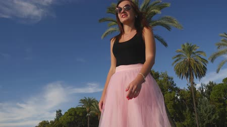 koketa : Fashion lifestyle portrait of young happy pretty woman in pink tulle skirt on blue sky and palm background