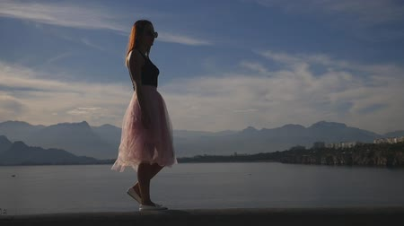 koketa : Fashion lifestyle portrait of young happy pretty woman in pink tulle skirt walking on blue sky background in slow motion