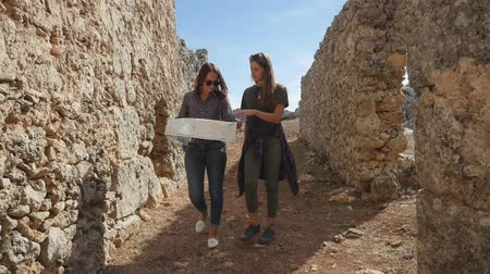 expedição : Two young girls walking with city map in the ancient city Lyrboton Kome in Turkey, slow motion Vídeos