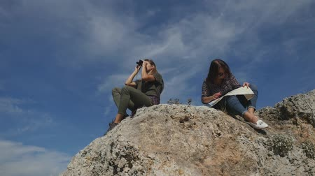 binocular : Young women tourists with map and binoculars looking far away sitting on the rocks