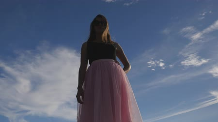 koketa : Fashion lifestyle portrait of young happy pretty woman in pink tulle skirt on blue sky background