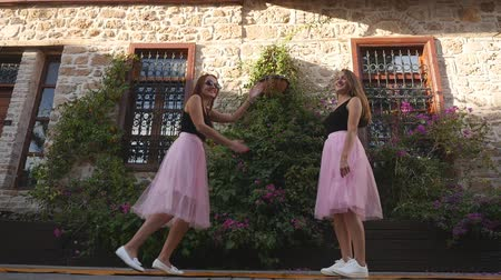 koketa : Fashion lifestyle two young happy pretty women in pink tulle skirt happily dancing on the street