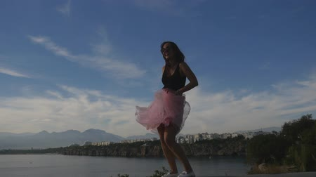 saia : Fashion lifestyle portrait of young happy pretty woman in pink tulle skirt dancing on blue sky background