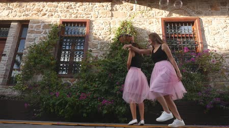 koketa : Fashion lifestyle two young happy pretty women in pink tulle skirt funnily meet each other in slow motion