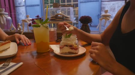 atender : Young women drinking lemonade and eating cakes at the cafe, closeup moving view, slow motion
