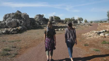 Two young girls walking in the ancient city Lyrboton Kome in Turkey