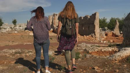 Two young girls walking in ancient city Lyrboton Kome in Turkey