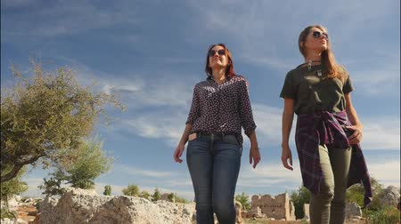 Two young girls walking in the ancient city Lyrboton Kome in Turkey, slow motion
