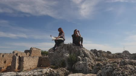 archeologo : Young women tourists with map and binoculars looking far away sitting on the rocks