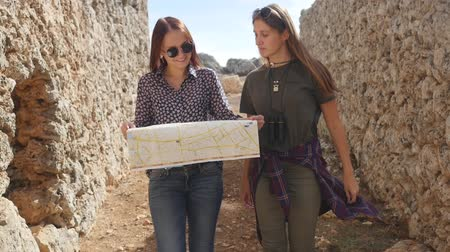 archeologo : Two young girls walking with city map in the ancient city Lyrboton Kome in Turkey
