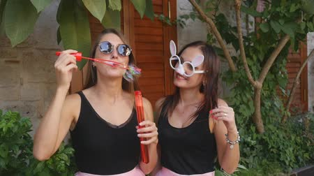 infantil : Two young funny women in pink tulle skirts and funny glasses blowing party bubbles at the camera outdoors on the street