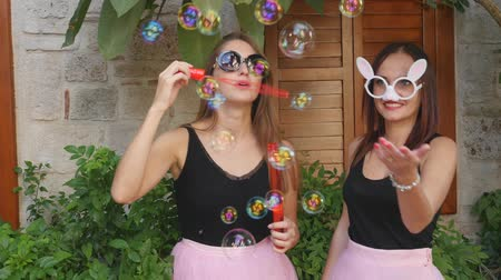 kifejező pozitivitás : Two young funny women in pink tulle skirts and funny glasses blowing party bubbles at the camera outdoors on the street