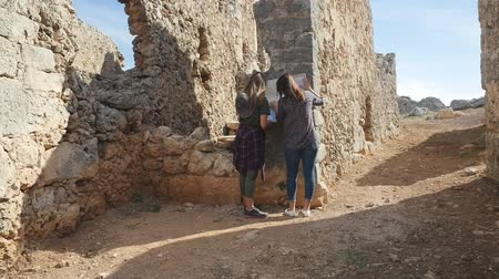 antalya : Two young girls walking with city map in the ancient city Lyrboton Kome in Turkey