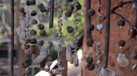Handmade beads from seashells hanging on a rope with old house on background