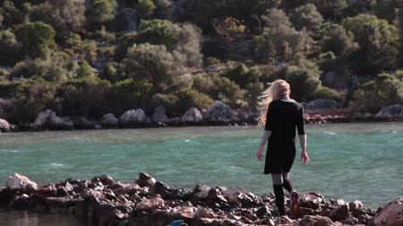 Young woman in black wear because of strong wind walking carefully on natural stone pier lake and mountains on background. Stok Video