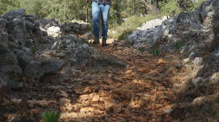 Hiker in blue jeans with backpack walking along the road strewn with small stones Stock mozgókép