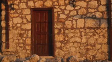 Stone house wall with wooden door in sunset and human shadow on it