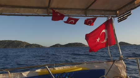 Closeup view of the flags of Turkey (red flag with white star and crescent) fluttering on blue sky background on the cruise boat with mountains on background