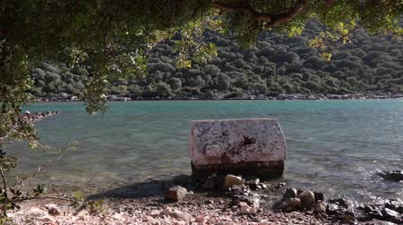 Ancient greek stone tomb on the sea shore washed by water in Kekova. It was looted many years ago
