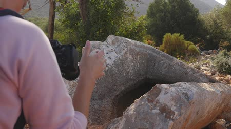 Young woman shooting on camera a part of ancient greek stone tomb in forest. It was looted and crushed many years ago 動画素材