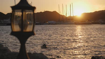 Luxury yachts rest in the port at sunset with small street lamppost on fhe front