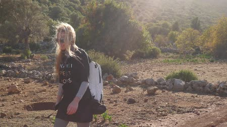 greek : Hiker woman with backpack walking along the road strewn with small stones