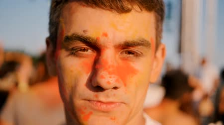 jump away : Closeup of young calm man in colored powder on the Holi Festival