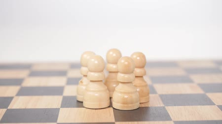 porażka : Womans hand holds brown queen figure and takes down brown pawns