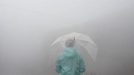 plášť : Back view of lonely young woman tourist in hat with transparent umbrella looking at breathtaking view of high mountains dissapearing in fog Dostupné videozáznamy