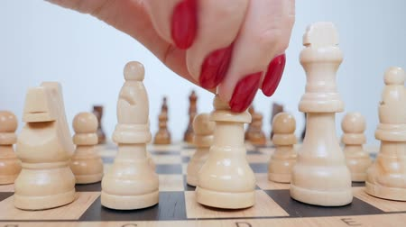 hierarchy : Womans hand setting up white queen figure on the board. Stock Footage