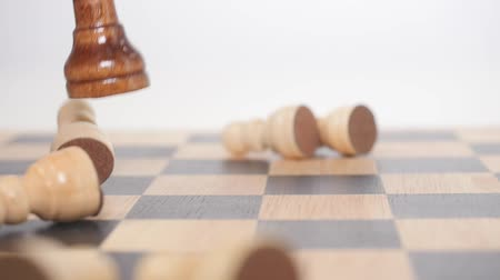 estratégico : Womans hand holds brown queen figure and takes down white pawns