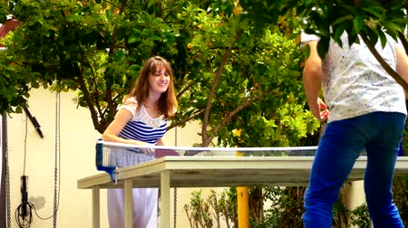 teniszütő : Happy young couple playing table tennis outdoors Stock mozgókép
