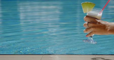 turmix : Womans hand puts cocktail by the swimming pool. Summer holidays, travel, vacation concept. Stock mozgókép