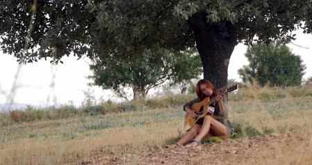 akusztikus : Woman playing guitar under the tree on beautiful sunny day