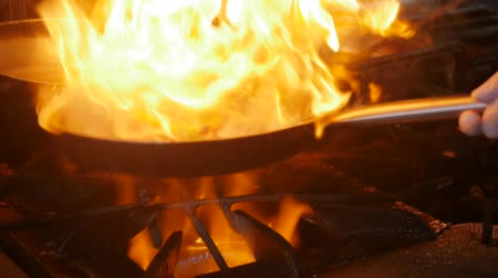 inclusive : Chef in restaurant kitchen at stove with pan, doing flambe on food. Fire in the kitchen. Fire gas burn is cooking on iron pan,stir fire very hot Stock Footage