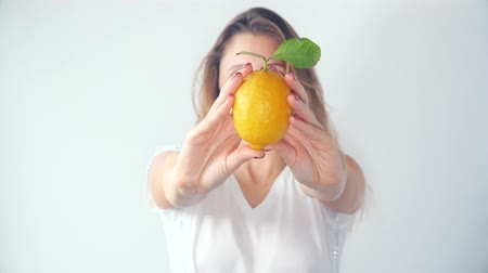 давать : Defocused young woman holding fresh bright lemon